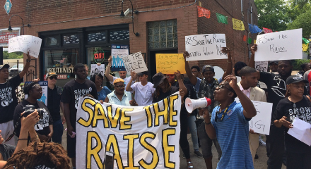 St. Louis rally to save the raise with large crowd with signs, banners, and someone speaking in a bullhorn