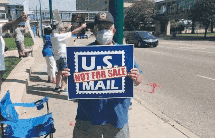 Solidarity with USPS and postal workers - individual holding a sign of US MAIL not for SALE